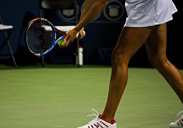 テニスコートでサーブをする女性